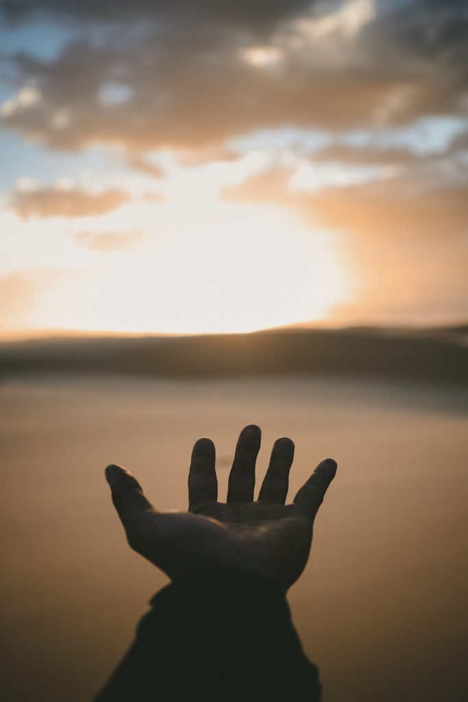 Hand reaching toward a sunset