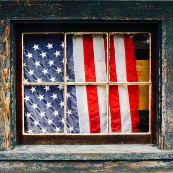 An American flag hanging behind a rustic window